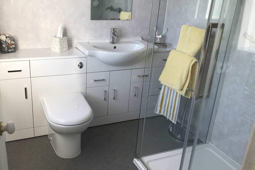 Example of the Type of luxury bathrooms we can install in Tamworth homes - shows modern white bathroom suite with sink and toilet embedded into wall of cabinets and a walk in shower with whole room sealed as wet room